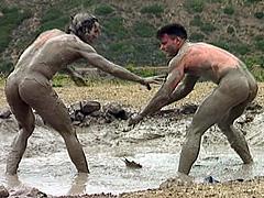 Naked men mud wrestling